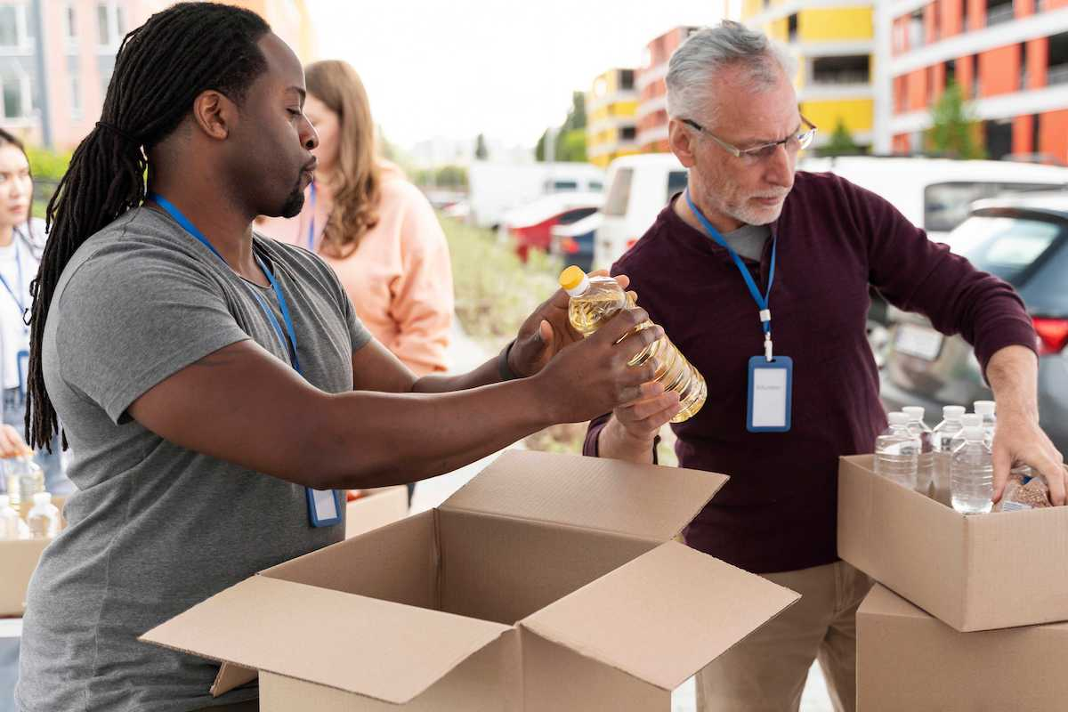 Two non-profit workers packing boxes of water bottles
