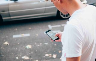 Man in white t-shirt looking at Uber app on mobile phone
