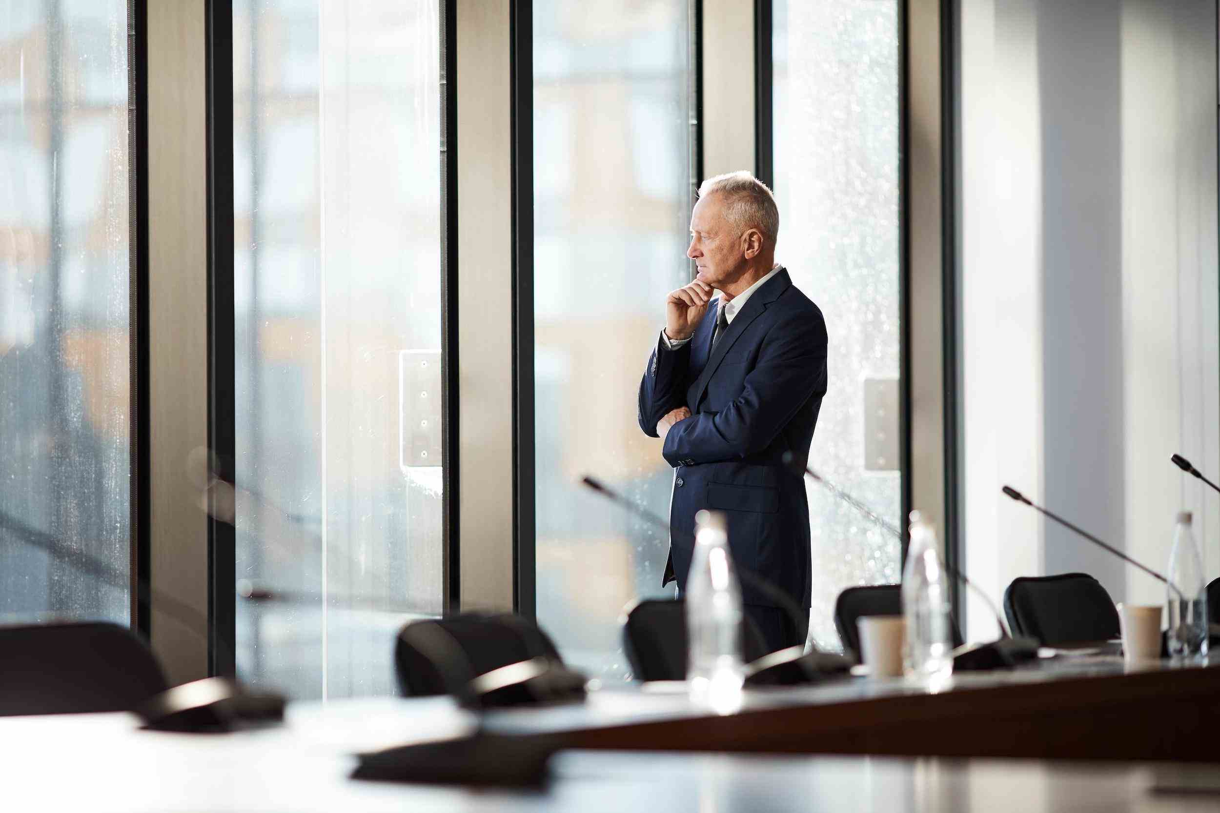 Senior caucasian man looking out office window thinking about common litigation risks